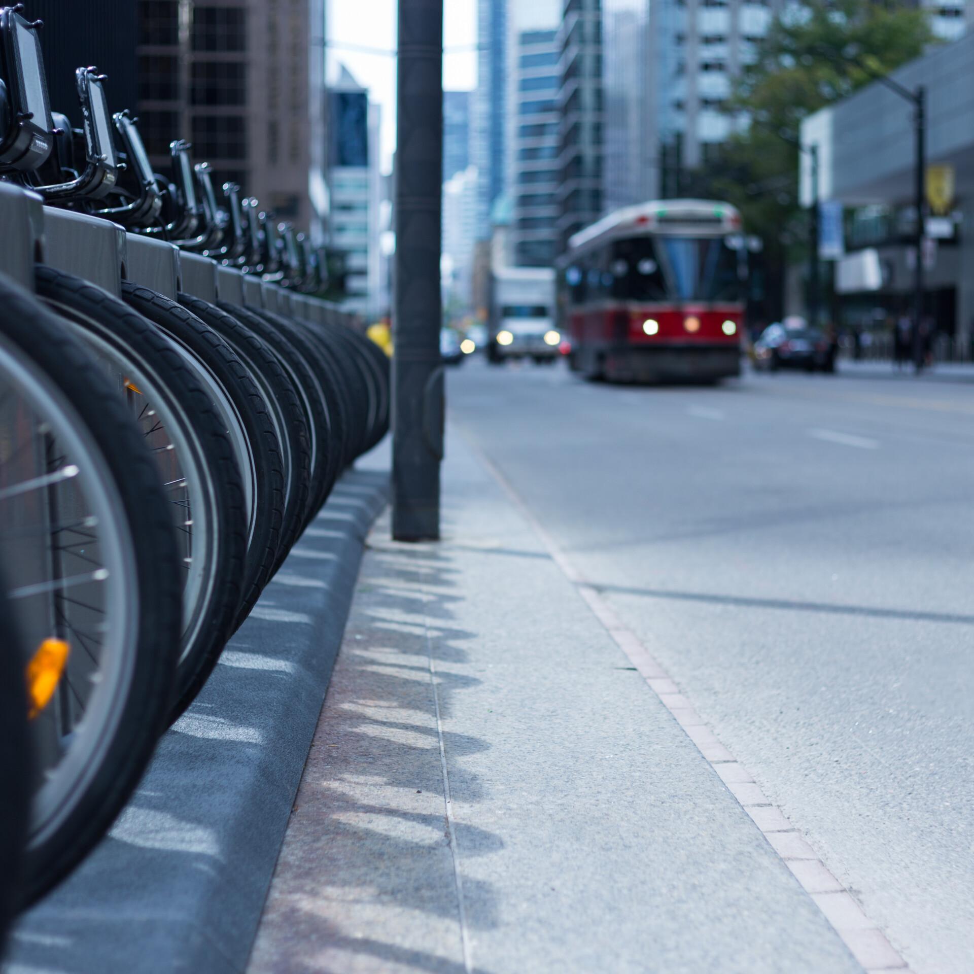 Straßenbahn, Fahrräder und Autos in einer Großstadt