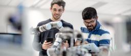 Zwei Mitarbeiter an einem Roboterarm